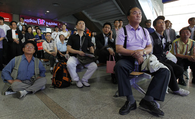 People react as they watch television news on losing communication with the Korea Space Launch Vehicle-1, or Naro-1, at the Seoul railway station