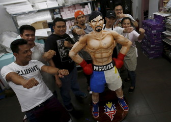 Workers from a bakery pose next to a life-size 70-kg chocolate cake of local boxing icon Manny Pacquiao for the media in Manila