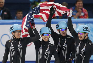 Members of the second-place United States team celebrate after the men's 5,000 metres relay short track speed skating final event at the Iceberg Skating Palace during the 2014 Sochi Winter Olympics