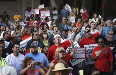 Gas company workers and their supporters chant in protest of possible wage and benefit cuts in Los Angeles