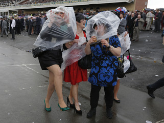 Racegoers take shelter from the rain during the second day of the Grand National meeting at Aintree in Liverpool
