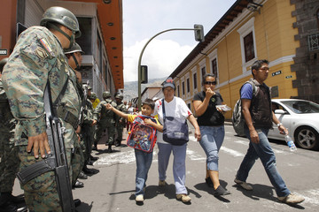 Military officers stand guard on the streets of Quito
