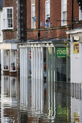 Residents look out their first floor window on a flooded street in Tadcaster, northern England