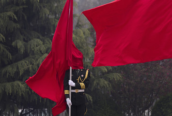 A flag is seen covering the face of a honor guard during a welcoming ceremony at the Bayi Building in Beijing
