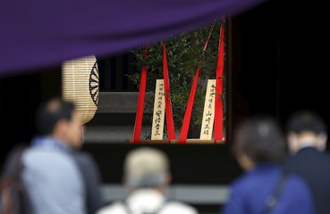 "A wooden sign which reads ""Prime Minister Shinzo Abe"" is seen on a ritual offering, a masakaki tree, from Abe to the Yasukuni Shrine in Tokyo"