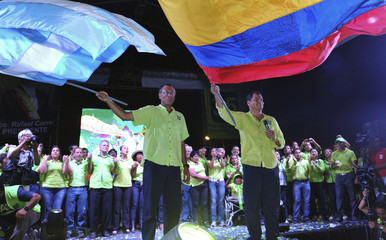 Ecuador's President Correa waves the national flag next to vice presidential candidate Glass during his closing political rally in Guayaquil