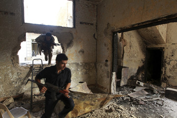Free Syrian Army fighters run through a hole in the wall in a damaged building in Aleppo