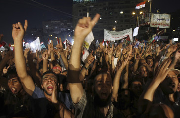 Islamists, members of the brotherhood, and supporters of Egyptian President Mohamed Mursi shout slogans with brotherhood's flag during a protest around the Raba El-Adwyia mosque square in the suburb of Nasr City