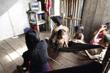 Victims of sexual abuse who used to work picking up rubbish at the beach watch television at home in Preah Sihanouk province