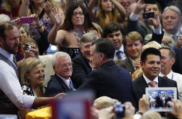 Republican presidential nominee Mitt Romney greets delegates as he arrives in the convention hall to accept the nomination during the final session of the Republican National Convention in Tampa