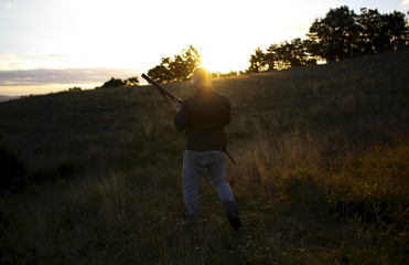 A hunter walks at sunrise during the first day of the Italy hunting season in Castell'Azzara