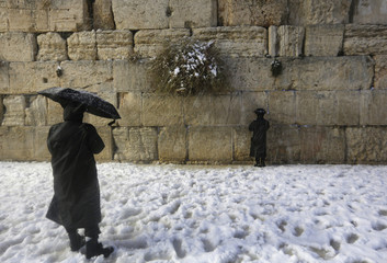 Ultra-Orthodox Jews visit the Western Wall in Jerusalem's Old City during a snowstorm