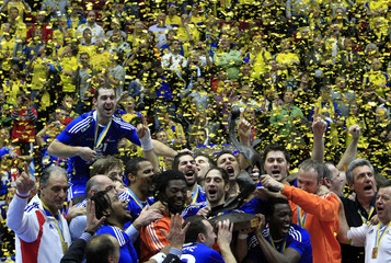 France's national handball team players celebrate on the winners podium with the trophy following their victory against the Denmark at the Men's World Handball Championships in Malmo