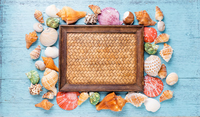 Frame with seashells on blue wooden background. Sea flat lay for mock up. top view
