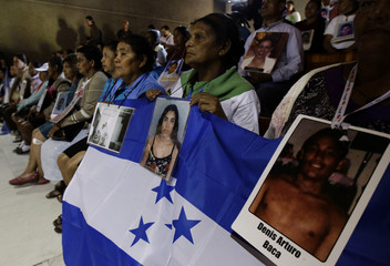 People hold up a Honduran flag with pictures of their relatives, who disappeared during their journey through Mexico to reach the U.S., during a mass in Mexico City