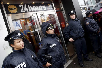 New York City Police officers (NYPD) stand by the entrance to a McDonald's as fast-food workers and their supporters join a nationwide protest for higher wages and union rights in New York