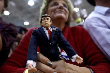 A supporter of Republican U.S. presidential nominee Donald Trump holds a Trump doll as she listens to Trump speak at a campaign rally in Ambridge