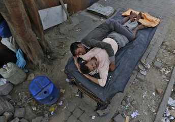 Men sleep on a closed street vendor stall at a roadside in New Delhi