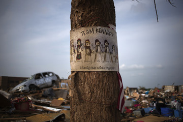 A drawing is left hanging on a tree in front of a home in Moore, Oklahoma