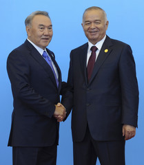 Kazakh President Nazarbayev welcomes Uzbek President Karimov during the Shanghai Cooperation Organization summit in Astana