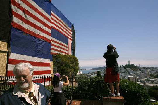 Tourists take in the view at the top of Lombard Street in the Nob Hill neighborhood in San Francisco