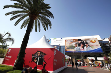 Visitors walk past the Festival palace where takes place the annual MIPCOM television programme market in Cannes
