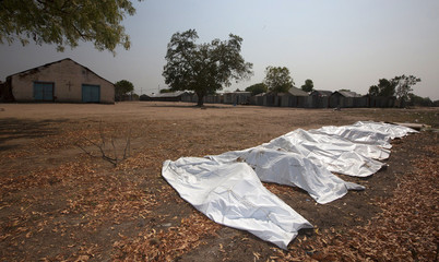 Decomposing bodies of fourteen women and two men are seen packed inside body bags at the St. Andrews Episcopal Church in Leodar district in Bor