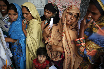 Women wait to vote at a polling station in a village near Lahore