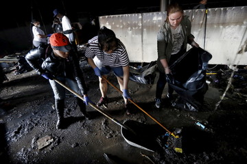 Members of the community clean up recently looted and burned CVS store amid concerns about the building's stability in Baltimore