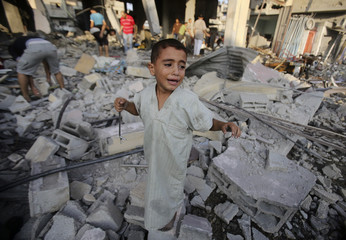 Palestinian boy cries as he stands in a debris-strewn street near his family's house in Rafah in the southern Gaza Strip