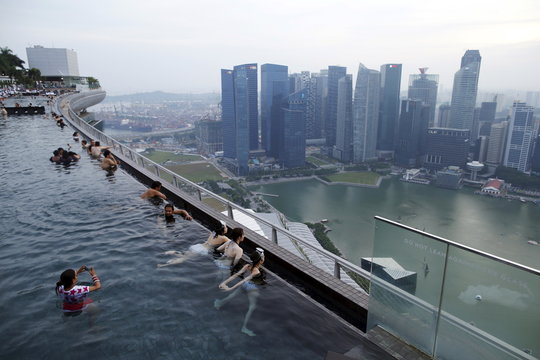 Tourists look out into the skyline of the city from an infinity pool atop the 57 storey high Marina Bay Sands hotel in Singapore