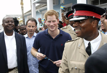 Britain's Prince Harry smiles as he walks during a tour of Harbour Island in Nassau