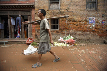 A vendor carries vegetables for sale at the ancient city of Bhaktapur