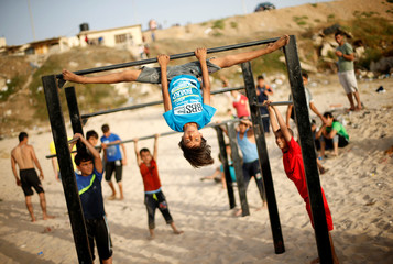 A Palestinian boy from Bar Palestine team demonstrates his street workout skills during a training session on a beach in Gaza City