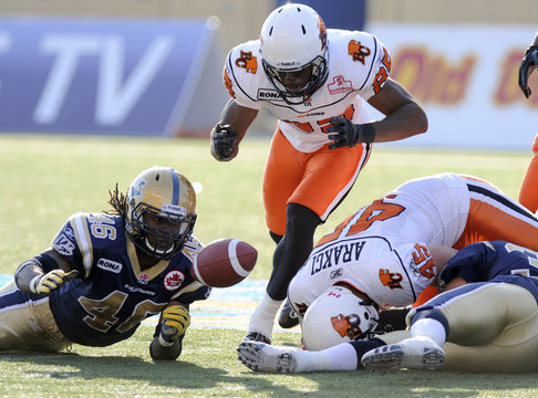 BC Lions Shawn Gore, Jason Arakgi and Winnipeg Blue Bombers Merrill Johnson chase a loose football during Canadian Football League action in Winnipeg