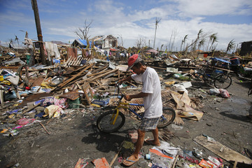 A man pushes his bicycle through debris in the Typhoon Haiyan devastated town of Palo