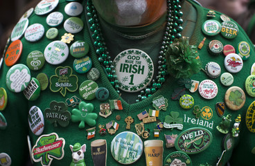 A man wears a sweater covered in Irish themed pins as he stands with thousands of spectators to watch the 254th New York City St. Patrick's Day parade up 5th Avenue in the Manhattan Borough of New York