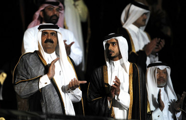 Qatar's Emir Sheikh Hamad applauds during the opening ceremony for the 2011 Asian Cup soccer tournament at Khalifa stadium in Doha