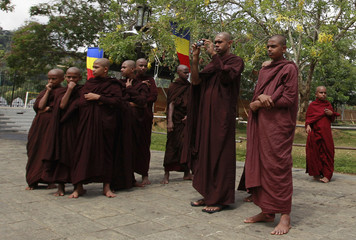 A group of Buddhist monks take pictures of the Sri Dalada Maligawa (Temple of the Tooth) in Kandy