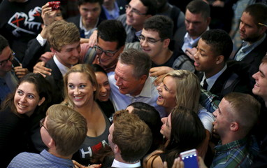 U.S. Republican presidential candidate John Kasich takes part in a group hug with supporters during a campaign stop in Chicago