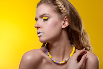 Portrait of a beautiful woman on a yellow background with creative make-up