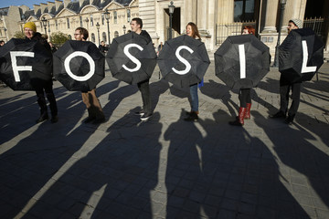 Activists stage a protest outside the Louvre pyramid in Paris