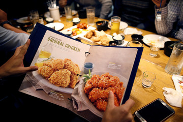 A man looks at a menu for fried chicken at a pub in Seoul