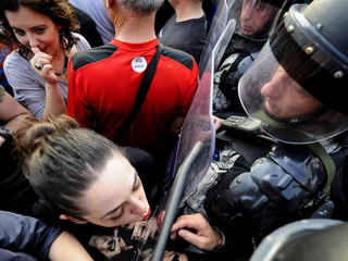 A girl puts lipstick and kisses the shield of the police in front of the Macedonian government building in Skopje