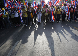 Anti-government protesters hold Thai national flags during a rally on a main road leading towards the Government House in Bangkok