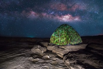 camping tent glows under a night sky full of stars. Outdoor Camping adventure.