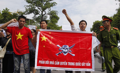 Policemen look at protesters holding a Chinese flag with a picture of a pirate skull and crossbones during an anti-China demonstration in Hanoi