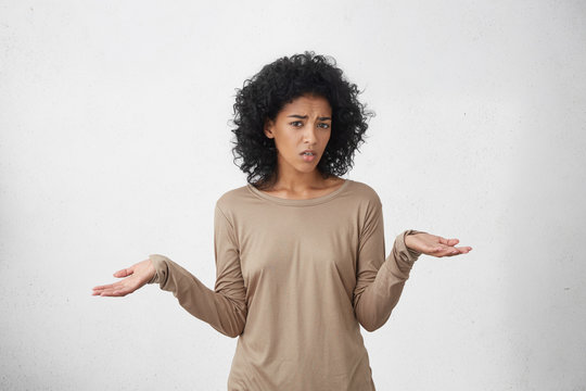 So what, Who cares. Unsure doubtful dark-skinned woman with black shaggy hair shrugging her shoulders in questioning gesture of uncertainty and keeping mouth opened, having confused clueless look