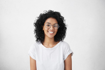 Pretty female with dark skin and broad happy smile wearing big round eyeglasses enjoying good positive news concerning her promotion at work, posing isolated against white blank wall background