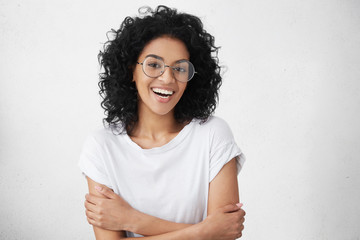Cheerful young good looking woman with clean dark skin and black shaggy hair posing indoors with crossed arms, smiling broadly with her white straight teeth, laughing at good joke, wearing casual top